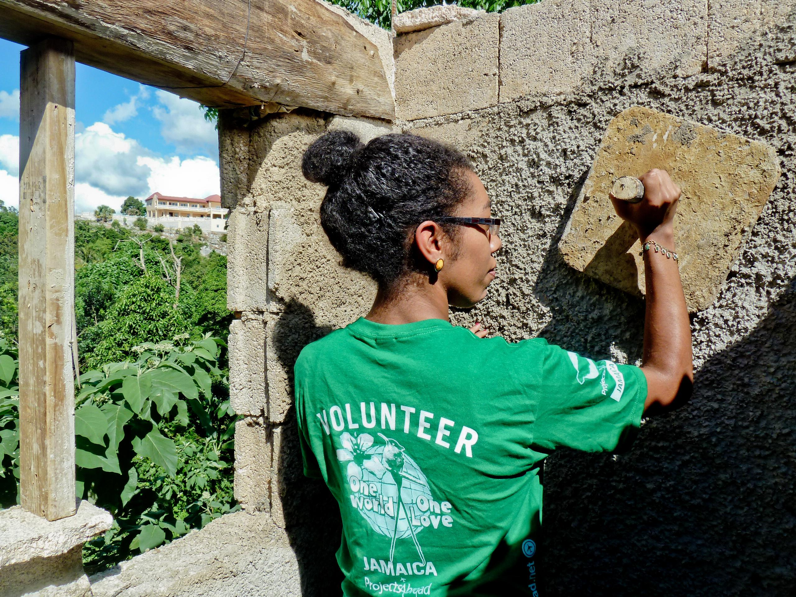 A female volunteer with Projects Abroad can be pictured helping with plastering as part of her building volunteer work in Jamaica.